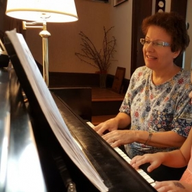 Teacher plays a duet with a budding piano student.