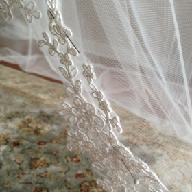 Applying Alencon lace to veil. Beginning stages of pinning in place.