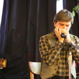 Clint playing the blues harp in concert