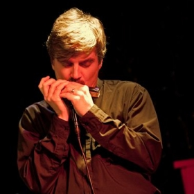 Clint playing the chromatic harmonica  in concert with East Side