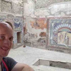 Standing in front of an exquisitely well preserved mosaic of an ancient Roman villa in Herculaneum, Italy.