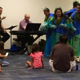 Performing as music director and pianist of a children's opera at a public library branch in Austin, TX.