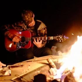 I love playing the guitar around the campfire with my friends.