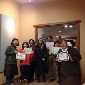 Adults with their English class completion certificates.