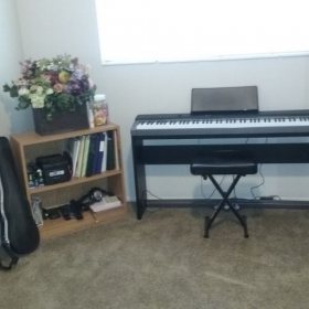 Home studio. Includes a mirrior, music stand, digital keyboard, my personal violin, candy, stickers, recliner chair, and other essentials.