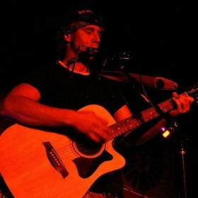 Playing the harmonica and acoustic guitar during a show in Missouri