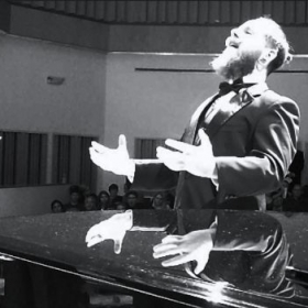 "B&W screenshot of a video taken while conducting ""Dachrilis Simghera"" with the WSU Men's Glee Club Oct. 16th 2017"