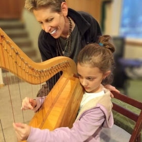 Harpist Anne Roos teaching harp lessons to 7-year-old