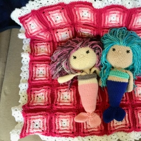 Two little mermaids on a crochet baby blanket