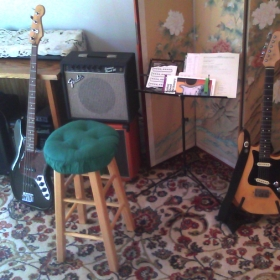 comfortable home studio equipped with guitars, amps, keyboard, drum machine and more