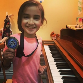A current piano/vocal student of mine. This is the medal she earned for achieving above a 90% on her piano theory exam.