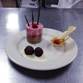 Plated dessert, Chocolate, strawberry mousse. Caramel dipped cookies, Chocolate ganache truffles in a cream vanilla sauce