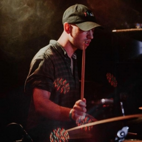 Me playing at the Larimer Lounge with my band. Looks like fun right! I can teach you the skills to get better at the drums.