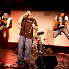 Chris performing with Hotel Hurry while bassist, Rinaldo, and guitarist, Anthony, perform epic dual jump kicks!  ;-)