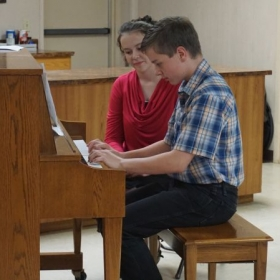 Playing Minuet in G at his first piano recital with me