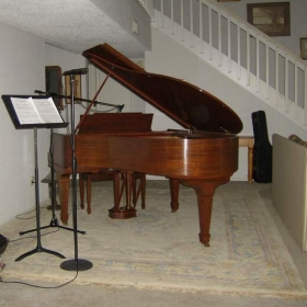 In-home studio equipped with baby grand, microphones, guitars and ukulele.