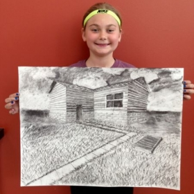 Charcoal drawing student learning about 2 point perspective and value.