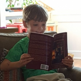 Isaac devouring The Enlightenment of Clive, the Misunderstood Warthog, the first in my children's vocabulary-intense, social values series.