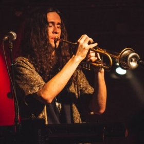 Playing a muted trumpet solo, live in Bloomington, IN (2018)