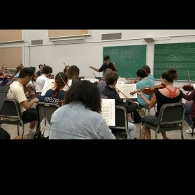 Conducting rehearsal with All-University Orchestra
