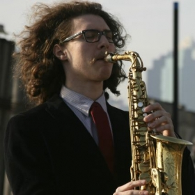 James playing sax for an event downtown.
