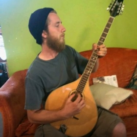 Playing an Irish Bozouki, similar to a mandolin but larger and tuned differently.