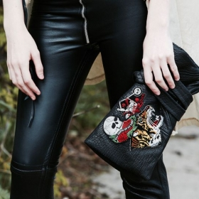 Close-up of handbag design with patches; shown also leather skinnies.