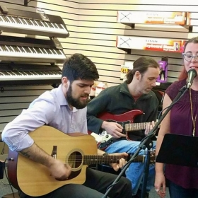 Singing with my bluegrass band at an open mic night event