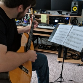 """Working on a solo guitar transcription of Debussy's """"Clair de Lune"""" in my studio."""