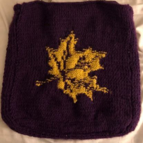 Knitted purple bag with a yellow maple leaf