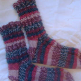Knitted socks: cuff down, one skein, lace pattern. Not a good beginner sock, inquire for a beginner sock lesson on Vanilla socks!