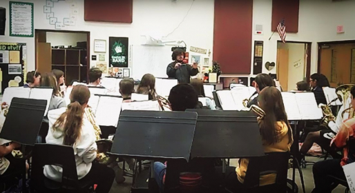 Conducting a middle school band class.