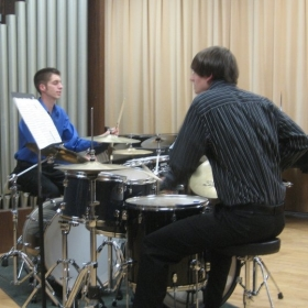 Performing a drum set duet.