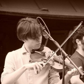 An old photo of me playing fiddle with the folk band Real Live Tigers!