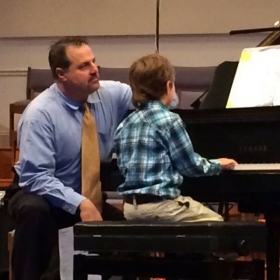 Helping Ben play his solo on his first piano performance on the Spring Recital 2014.