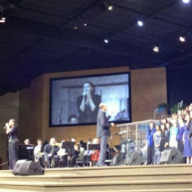 Leading a song as a worship leader at ALCF in California with a full choir and orchestra.
