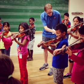 Teaching violin students in a class at Longy's El Sistema program.