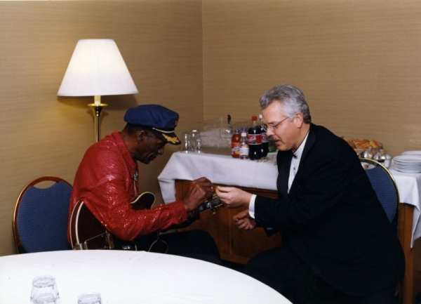 In 2001 I performed with Chuck Berry  Here is  Chuck handing me his guitar pick to help me tune his guitar.