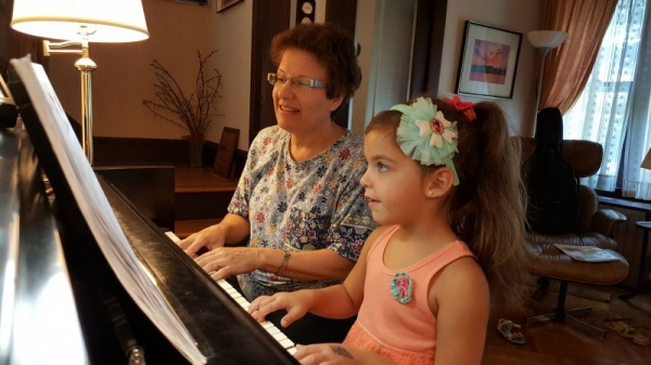 Teacher plays a duet with a partially hidden, but budding piano student.