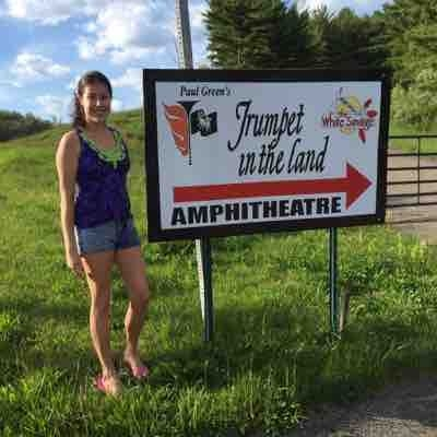 Sarah infront of the sign to one of the first professional companies she worked at!