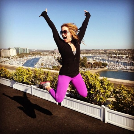 Certified Pilates + fitness instructor, Kimberly Spencer jumps for joy helping women love their bodies through Pilates.
