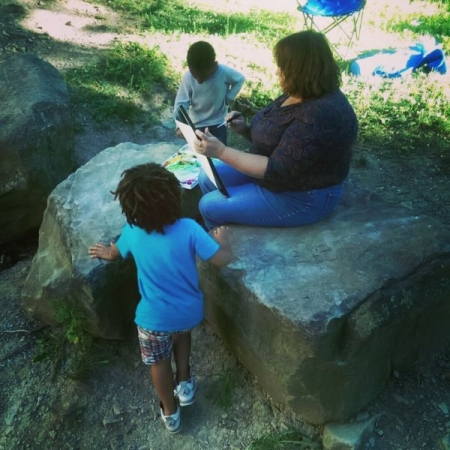 Little ones watching and painting with Jane as she sketching and paints outside in the park in Cleveland, OH.