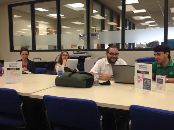 A picture of myself (middle) and my fellow writing tutors at work in the writing center, going over professional development materials.