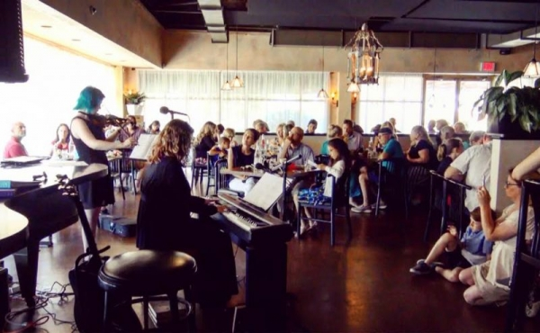 One of my awesome students performing in a recital at a packed restaurant (and me playing the piano)