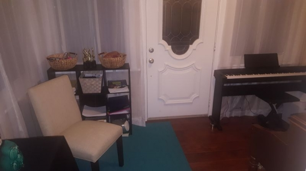My newly updated studio with a piano, a keyboard and a chair for those who wish to listen during lessons.