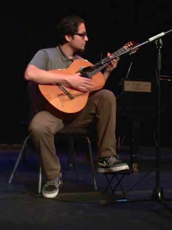 I'm performing on stage for a recital at Dominican University on a classical guitar.