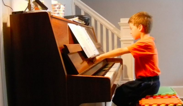 A student in Amy's studio checking to see that he is the correct distance from the piano!