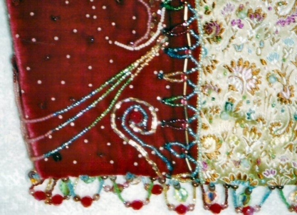 This is a closeup of a top made of vintage silk velvet, Chinese silk Brocade and a celestial scene in beads.