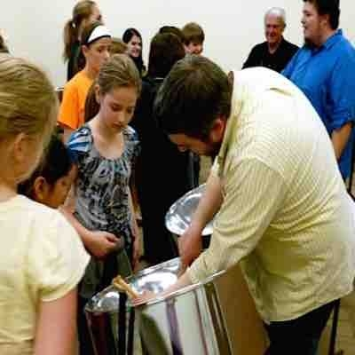 Teaching kids at a children's event hosted by the Marion Iowa Library how steel pans work.