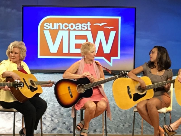 Sabine teaching guitar during the taping of the Suncoast View in Sarasota
